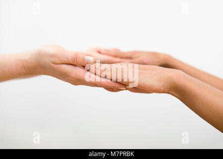 A close up of hands helping each other. In this case specifically for pilates. - Stock Photo