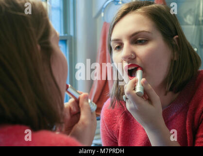A teenaged girl putting on lipstick. - Stock Photo