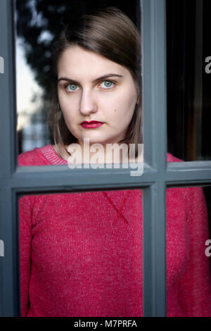 A teenaged girl looking out a window. - Stock Photo