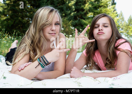 Two girls laying on a blanket making 'peace' and 'hang loose' hand symbols. - Stock Photo