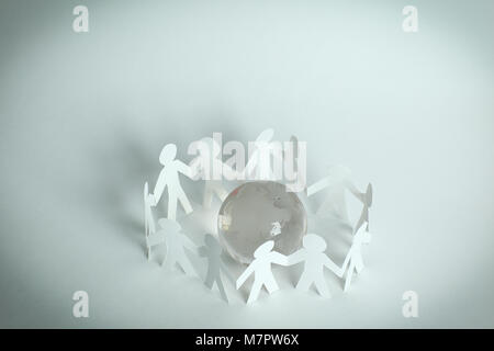 team paper men standing around the glass globe. - Stock Photo