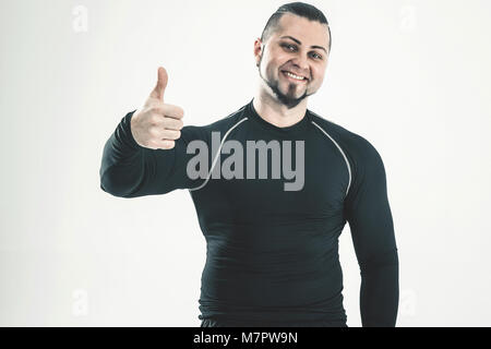 portrait of the instructor on bodybuilding shows thumbs up.t - Stock Photo