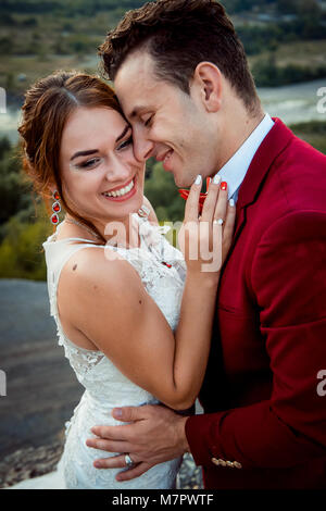 Emotional portrait of the cheerful newlyweds smiling and hugging outdoor. - Stock Photo