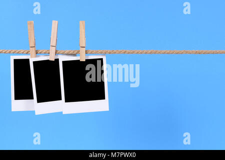 Several blank instant camera photo prints hanging on a rope or string isolated against a blue background.  Space - Stock Photo