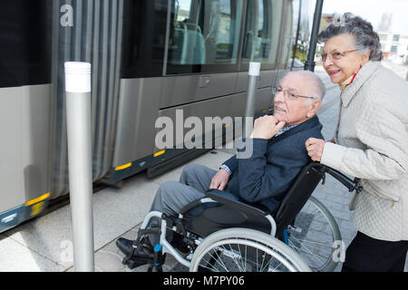Elderly woman pushing wheelchair bound husband onto tram - Stock Photo
