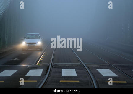 Single car on the road in front of crossing marking in heavy fog - Stock Photo