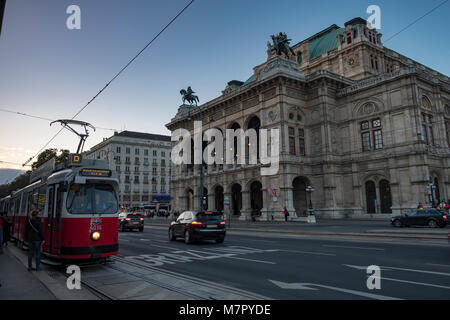 Old tram pulls away from stop with the Vienna Opera House Behind. Taken early evening in September as the city lights - Stock Photo