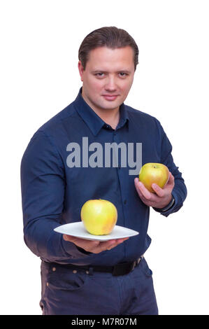 Portrait of young athletic elegant man offering one apple on white plate for you with one hand and holds another - Stock Photo