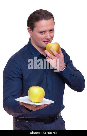 Portrait of young athletic elegant man with blue shirt offering one apple on white plate with one hand and eating - Stock Photo