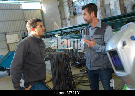 happy male worker showing something to coworker - Stock Photo
