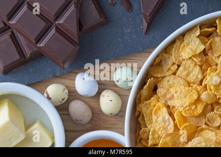 Easter corn flake cake ingredients with mini chocolate eggs top down view - Stock Photo