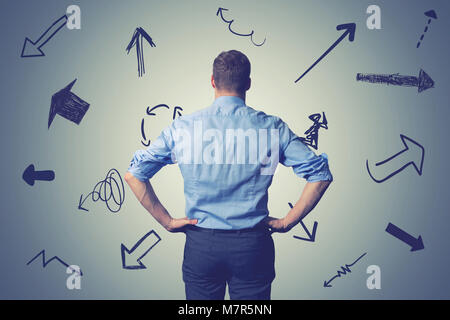 confused businessman with direction arrows. choosing the right way decision concept - Stock Photo