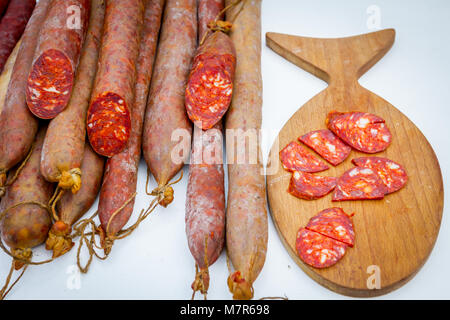 Slices of smoked sausages are placed on a cutting board in traditional style. - Stock Photo