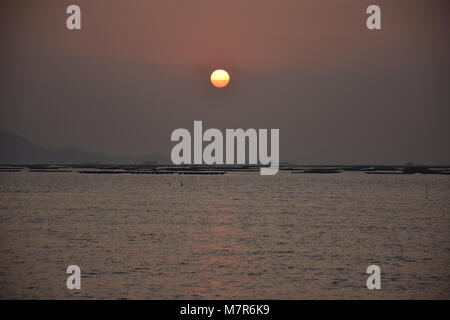 Sunset in Shenzhen bay seen from New Territories, Hong Kong - Stock Photo
