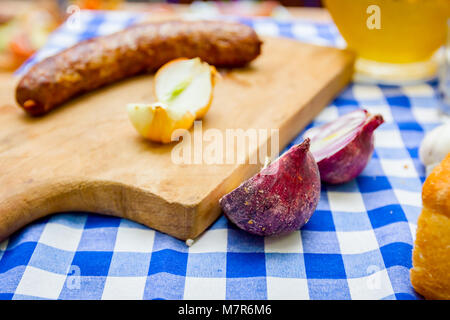 Roasted sausage with onion is placed on a cutting board in traditional style. - Stock Photo
