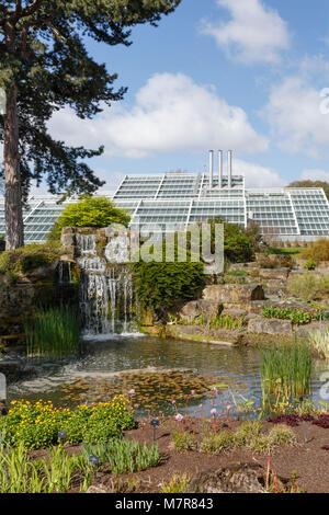 London, UK - April 18, 2014. Rock garden and Princess of Wales Conservatory in Kew Botanic Gardens. The gardens - Stock Photo