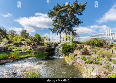 London, UK - April 18, 2014. Rock garden and Princess of Wales Conservatory in Kew Botanic Gardens. The gardens - Stock Photo