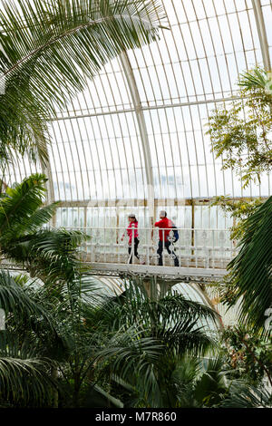 London, UK - April 18, 2014. Visitors walk around the interior of the Palm House at Kew Gardens. The gardens were - Stock Photo