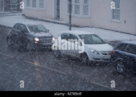 traffic chaos in UK with cars travelling along snow covered road during blizzard conditions - Stock Photo