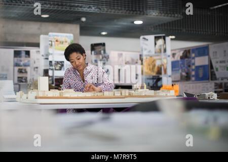 Female architect working on model - Stock Photo