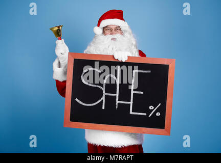Portrait of santa claus holding blackboard and bell - Stock Photo