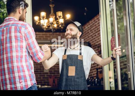 Cheerful barber greeting his male customer - Stock Photo
