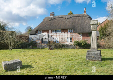 Charming thatched cottage and village green in Martin village in Hampshire, UK, with the replica year 2000 village - Stock Photo
