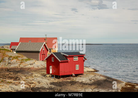 Small red cabin on the rocky shore of Ona Island - old fishing community in Sandoy Municipality in Western Norway, - Stock Photo