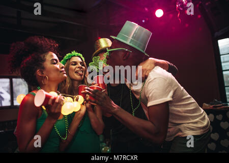 Group of cheerful friends having fun at bar. Multi-ethnic men and women partying and dancing at night club. Celebrating - Stock Photo
