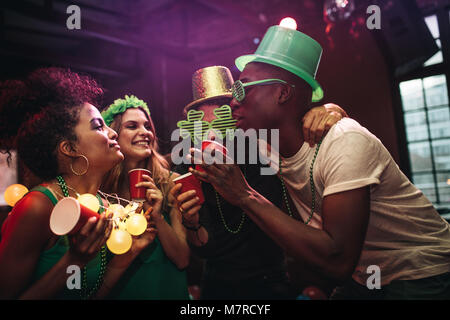 Multi-ethnic men and women having fun at the bar. Group of friends celebrating St. Patrick's Day at nightclub. - Stock Photo