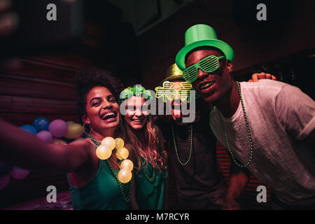 Group of friends enjoying at party in the bar and taking selfie with smart phone. Cheerful en and women partying - Stock Photo