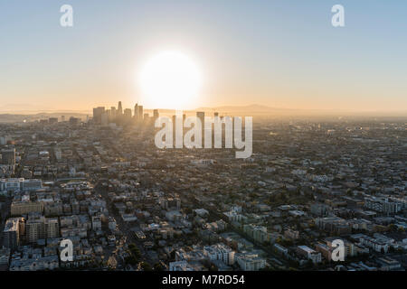 Aerial view of sunrise behind streets and buildings in the urban core of Los Angeles California. - Stock Photo