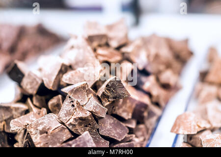 Pile of many milk dark brown chocolate pieces macro closeup chunks on tray glass display in candy shop store chocolatier - Stock Photo