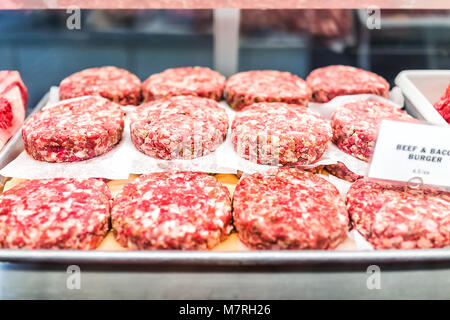 Many beef and bacon burger raw meat sausage patties on tray with pink chunks in butcher store shop - Stock Photo