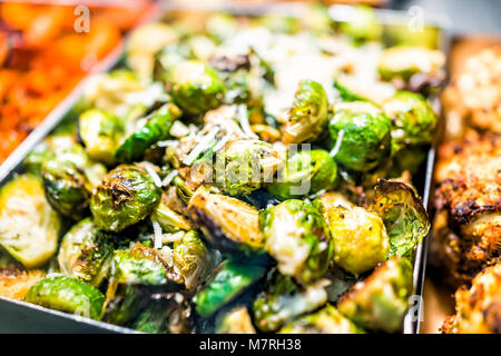 Macro closeup of roasted green brussels sprouts cabbage in tray on display in buffet, catering, deli, store, shop - Stock Photo