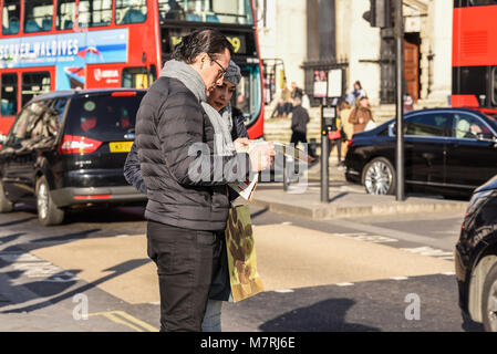 Tourists looking at map in London with red bus and traffic. Tourism. Male and female couple. People. Britain. British. - Stock Photo