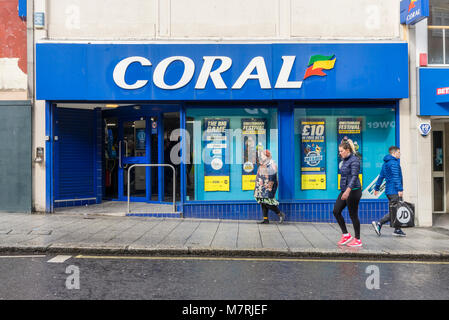 People walking past a coral bookmakers / betting shop facade on Southampton High Street, Southampton England, UK - Stock Photo
