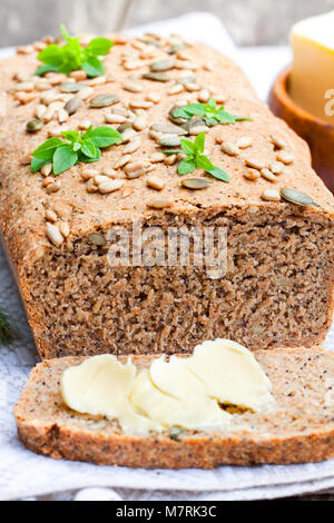 Homemade  sliced rye bread with sunflower seeds and fresh butter - Stock Photo