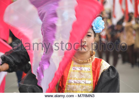 Karawang, West Java. Indonesia, 11 March 2018. A young girl performing flag acrobatic during Cap Go Meh parade - Stock Photo