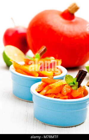 Caramelized  pumpkin and apple in small pot on white - Stock Photo