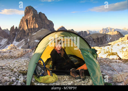 Female mountaineer sitting relaxed in tent and smiling happy after a night outside in the mountains. Great mountain - Stock Photo
