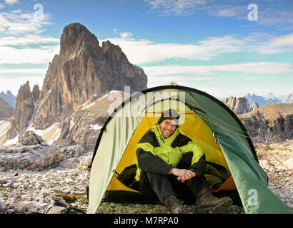 Male mountaineer sitting relaxed in tent and smiling happy after a night outside in the mountains. Great mountain - Stock Photo