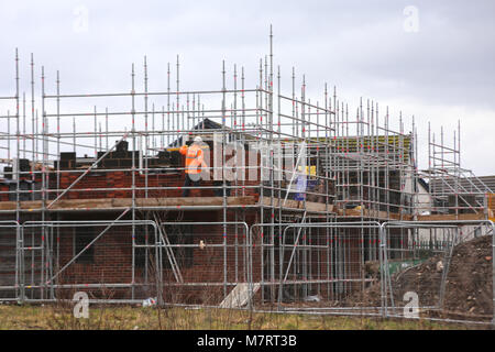 Bricklayer working on the construction of a new house in a residential development - Stock Photo
