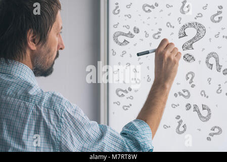Perplexed businessman drawing question marks on whiteboard in the office, selective focus - Stock Photo