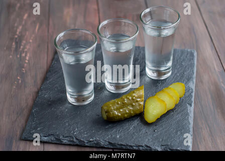 small Wine-glass of Russian vodka and salt cucumber snack on wooden table. copy space - Stock Photo