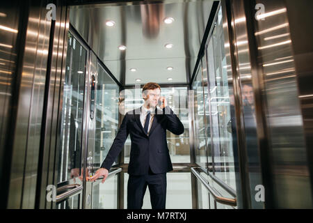 Smiling modern young businessman speaking on the phone while standing in elevator - Stock Photo