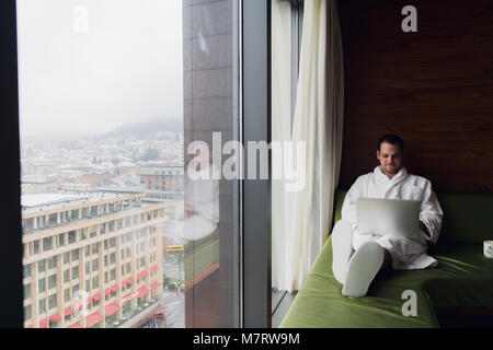 Businessperson working at home or in trip. Side view portrait of handsome young businessman sitting on bed and using - Stock Photo