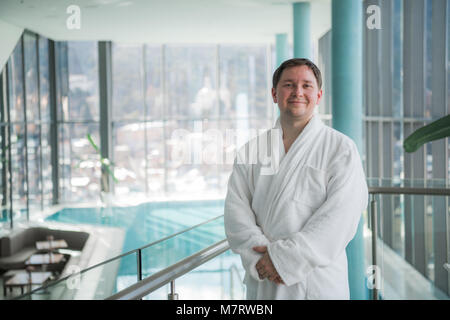 Adult man in a bathrobe standing in the spa in front of a pool - Stock Photo