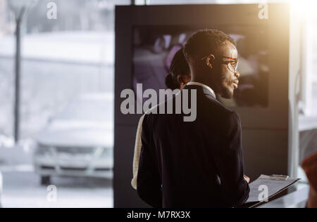 african Car dealer showing vehicle to black woman - Stock Photo
