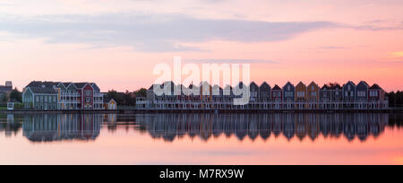 Row of Colorful houses in Houten, Netherlands, at dusk with reflections on Rietplas lake. - Stock Photo
